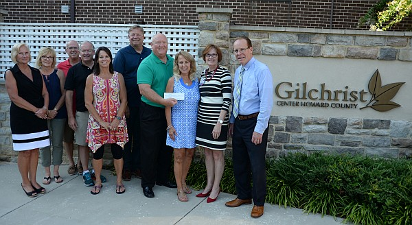 Board presenting a check to Gilchrist